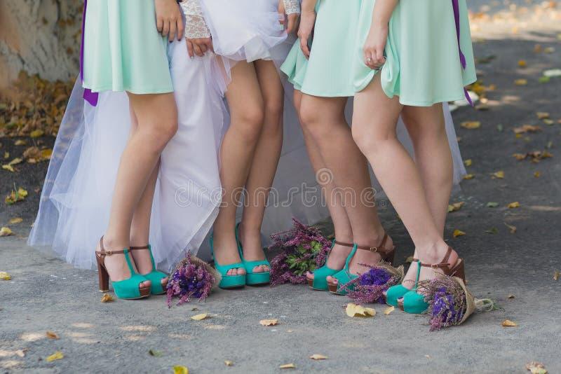 Benen van de bruid en de bruidsmeisjes, en bloemboeketten stock foto