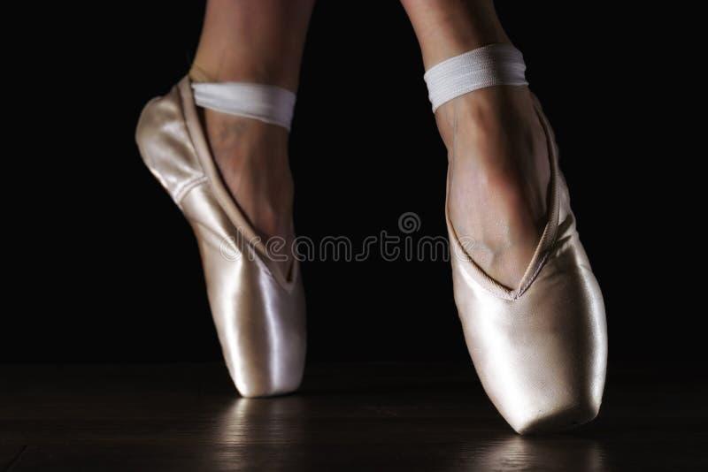 Benen van de close-up de klassieke ballerina ` s in pointes op de zwarte vloer stock afbeeldingen
