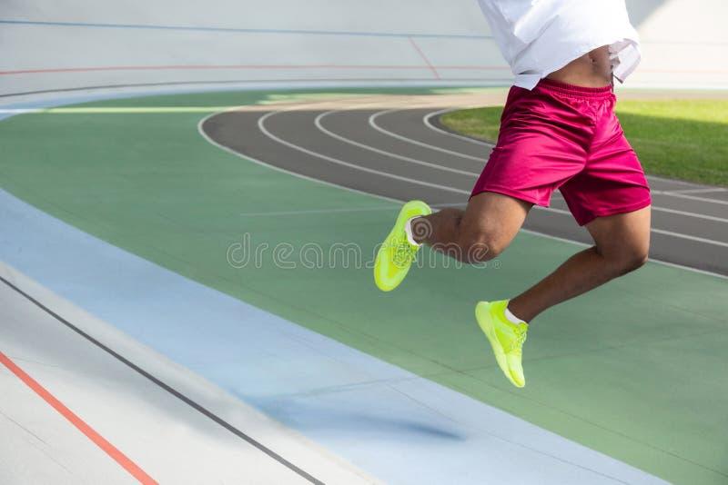 Benen van een Afrikaanse Amerikaanse sportman die in openlucht springen royalty-vrije stock foto's