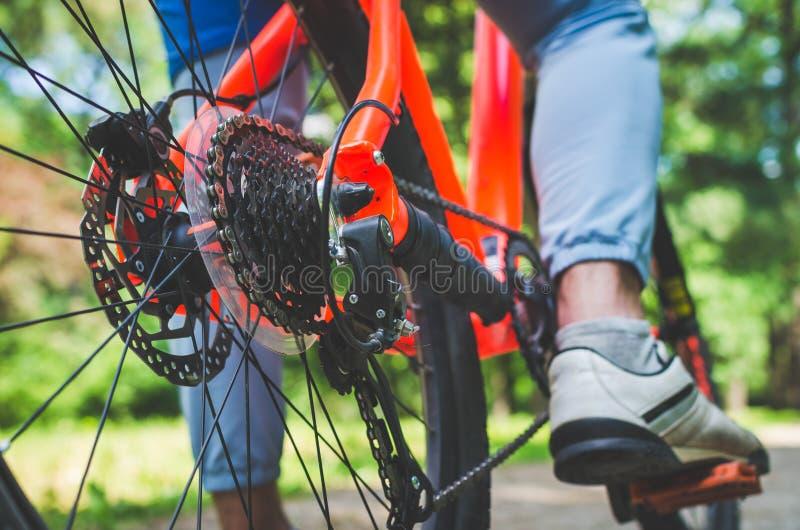 Benen van een fietser en een deel van een fiets op een landweg stock afbeeldingen