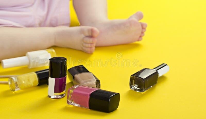 Benen van een klein meisje en schoonheidsmiddelen op een gele achtergrond stock foto's