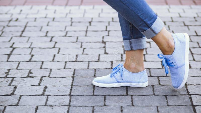 Benen van een meisje in jeans en blauwe tennisschoenen op een stoeptegel, een jonge vrouw die in een de zomerpark wandelen stock fotografie