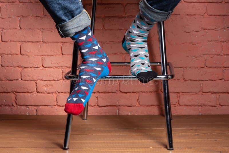 Benen van een mensenzitting op een hoge stoel, in sokken van verschillende kleur, close-up, concept, tegen een bakstenen muur royalty-vrije stock afbeeldingen