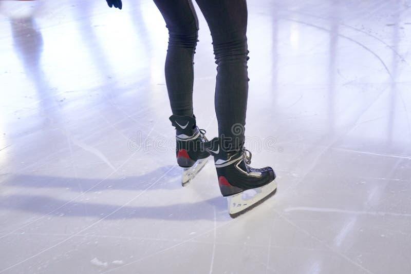 Benen van een vrouw die op een ijsbaan schaatsen stock foto