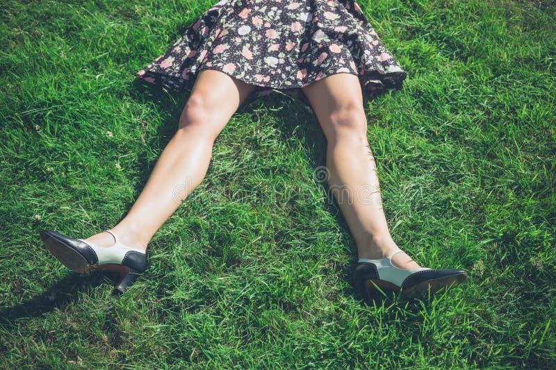 Benen van het jonge vrouw liggen op gras in gebied royalty-vrije stock foto's