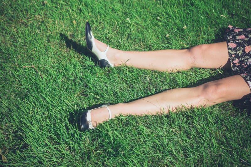 Benen van het jonge vrouw liggen op gras in gebied royalty-vrije stock foto