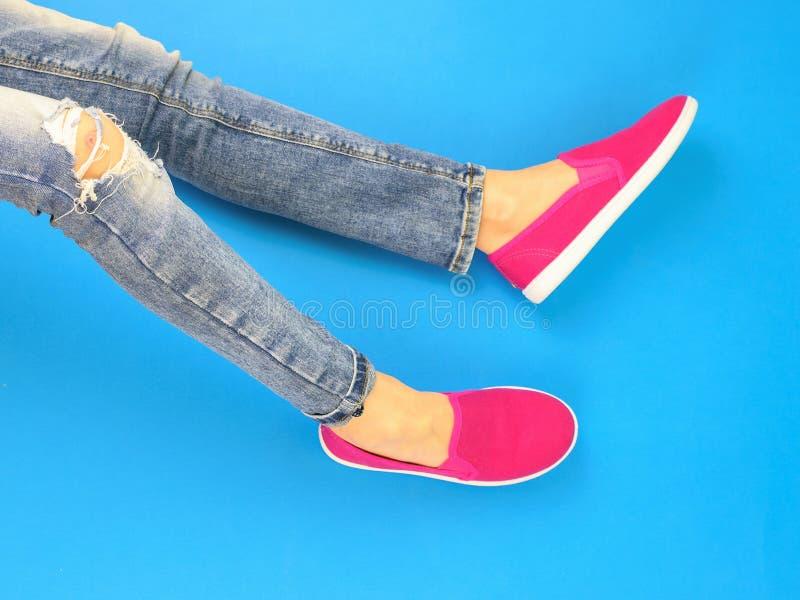 Benen van het meisje met een gebroken knie in gescheurde jeans op de blauwe vloer De mening vanaf de bovenkant royalty-vrije stock foto