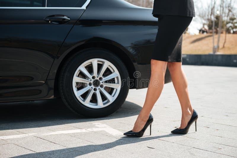 Benen van onderneemster met hoge hielenschoenen die dichtbij auto lopen royalty-vrije stock afbeelding