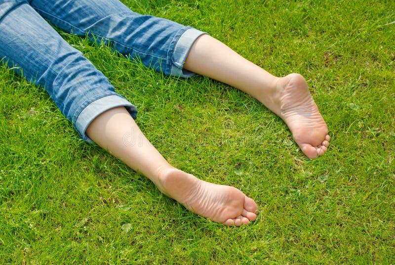 Benen van ontspannende vrouw in gras royalty-vrije stock afbeeldingen