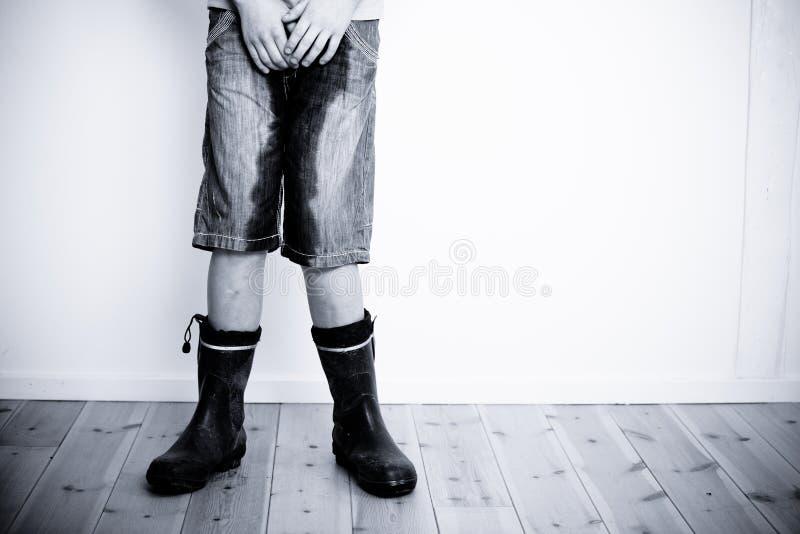 Benen van tiener met natte broek en laarzen stock afbeelding