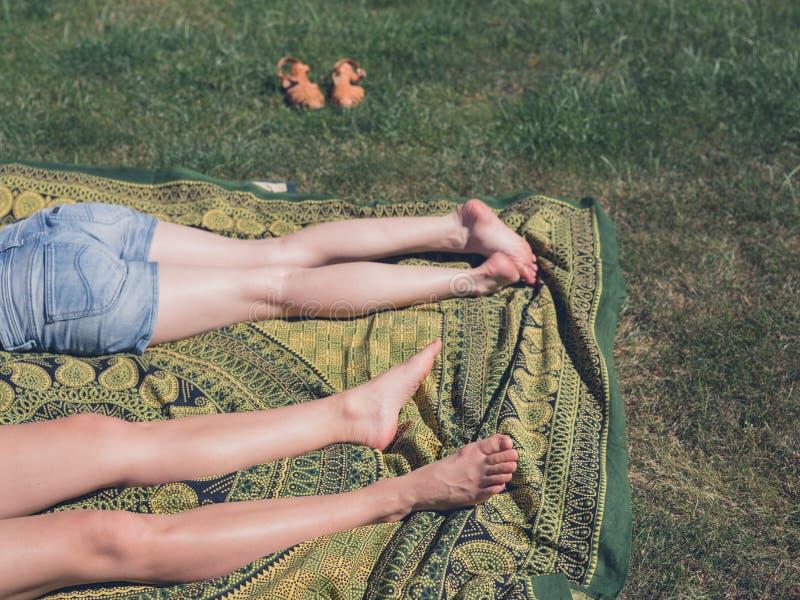 Benen van twee jonge vrouwen buiten op gras stock fotografie