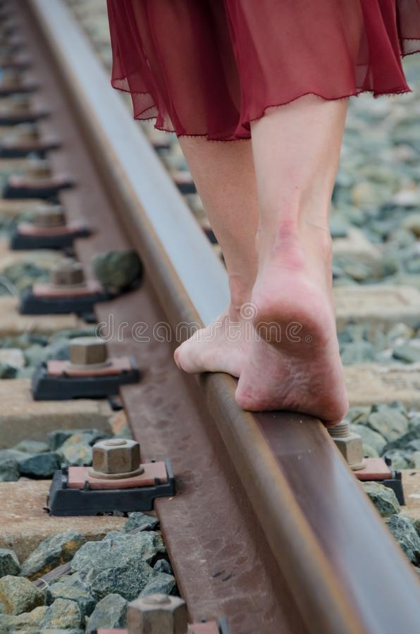 Benen van vrouw het lopen blootvoets op het treinspoor royalty-vrije stock afbeelding