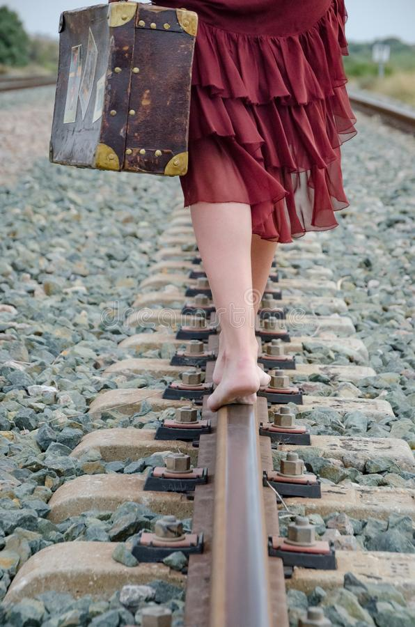 Benen van vrouw met koffer die blootvoets op het treinspoor lopen royalty-vrije stock afbeelding