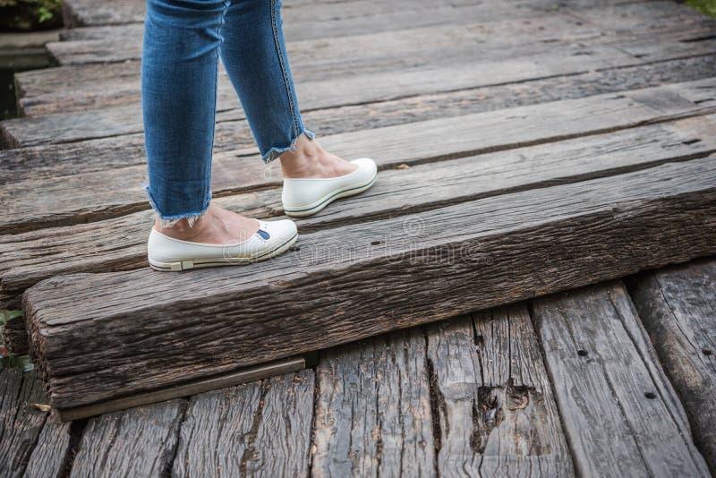 Benen van vrouwen die jeans en witte schoenen kleden stock afbeeldingen
