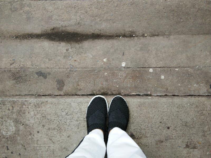 Benen in witte broeken, voeten in zwarte weefselschoenen die zich op vuile concrete vloer bevinden stock afbeelding