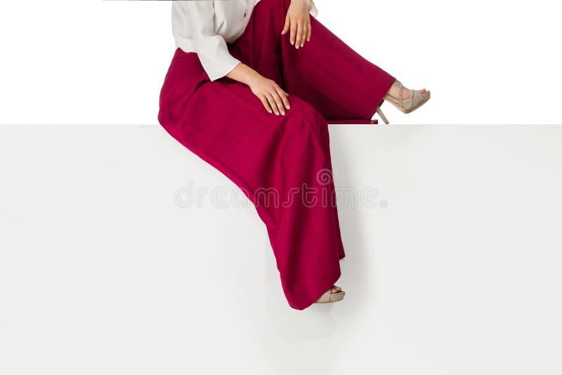 Benenvrouw die hoge hielenschoenen dragen die op bank zitten stock afbeelding