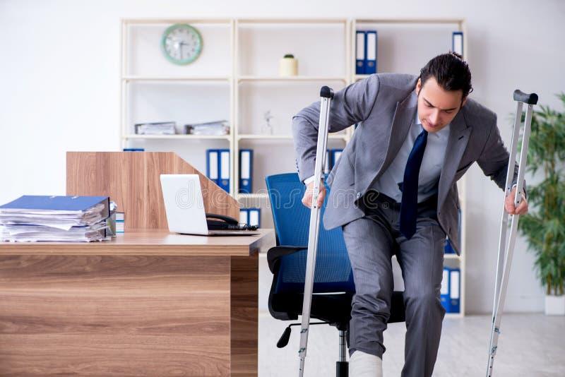 Benet sårade manlig anställd i kontoret royaltyfri bild