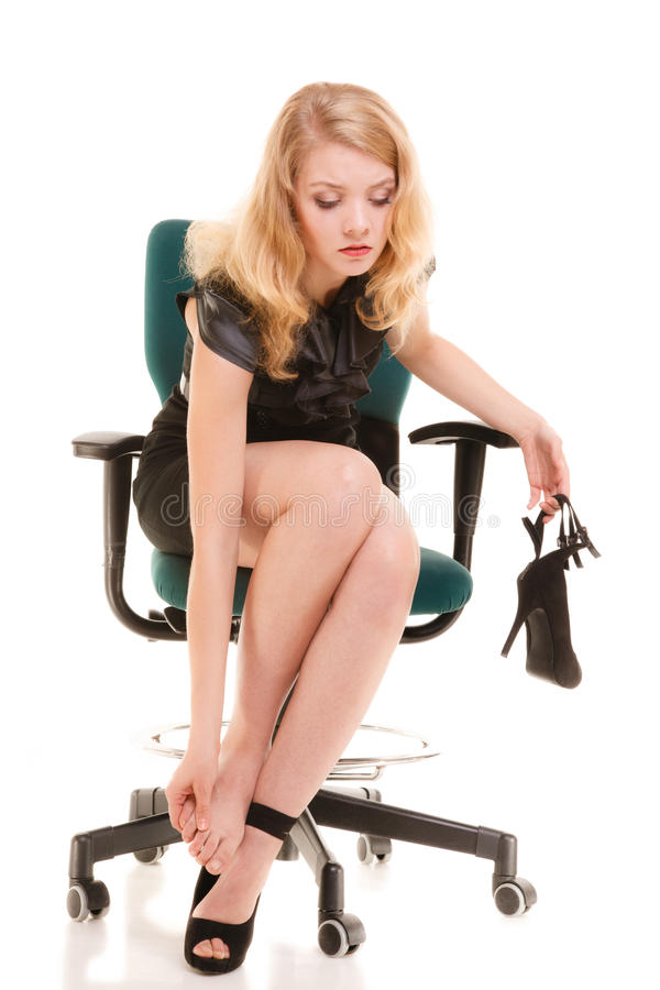 Benet smärtar, tröttade kvinnasammanträde på stol och masserafot royaltyfri foto