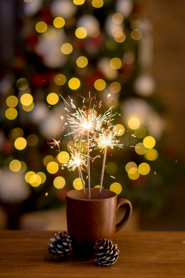 Bengal fire and colorful bokeh christmas, new year background lights. Close up royalty free stock photo