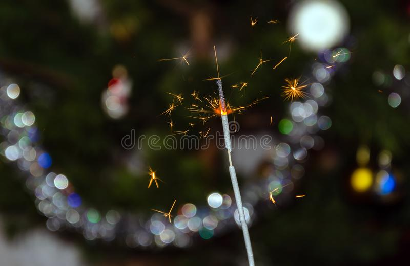 Bengal lights with flying sparks on the background of a Christmas tree stock photos