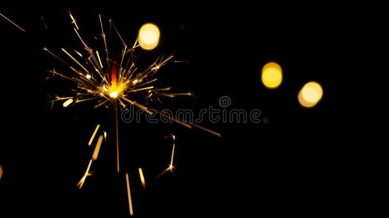 bengala ardiendo en fondo del bokeh de luces de la guirnalda fotografía de archivo