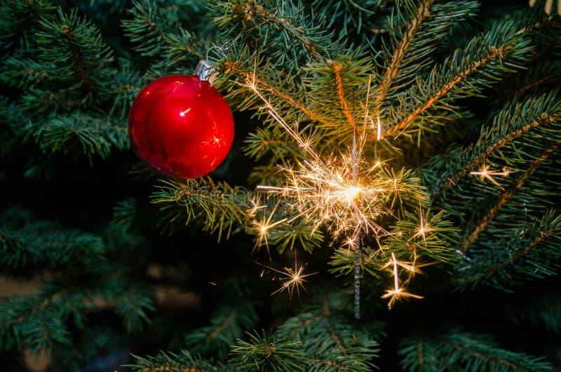 Bengala chispeante en el árbol de navidad imagenes de archivo