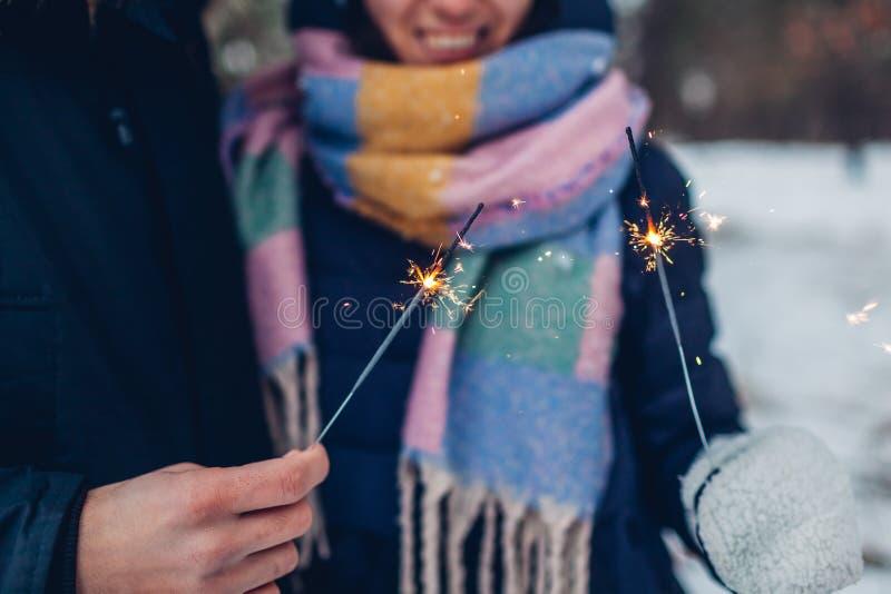 Bengalas ardientes de los pares cariñosos hermosos en la Navidad del bosque del invierno y el concepto del Año Nuevo foto de archivo libre de regalías