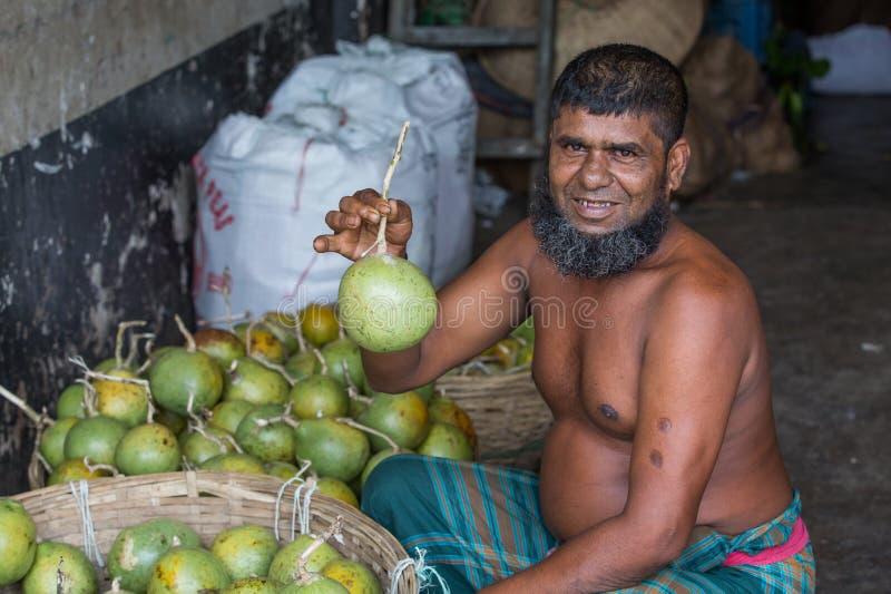 Bengalczyka Bael sprzedawca czekać na klientów przy hurtowym rynkiem przy karwan Bazar w Dhaka, Bangladesz obrazy royalty free