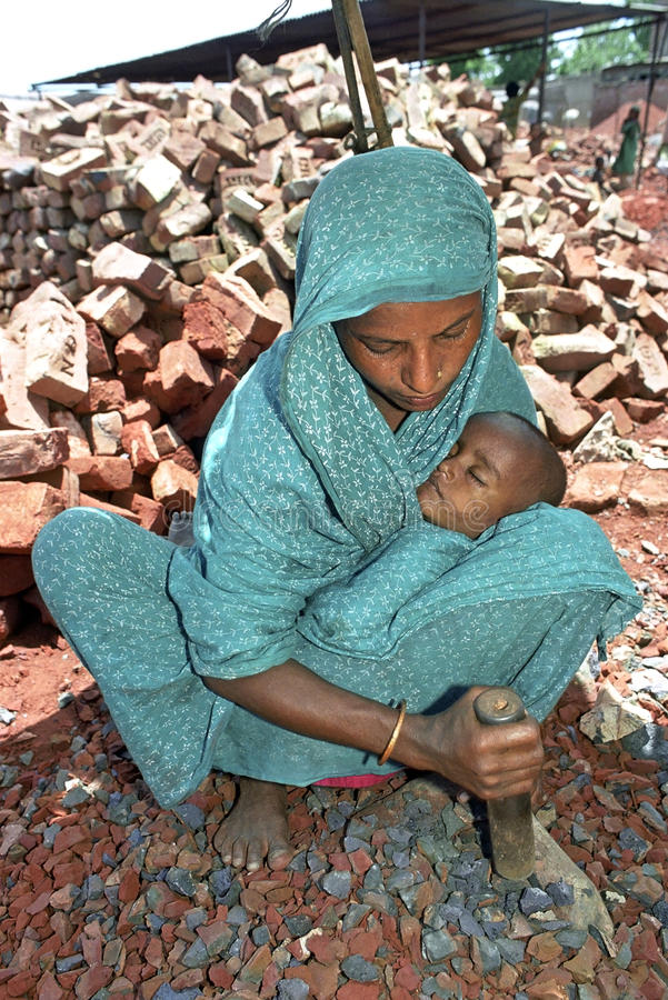 Bengali Mother with baby working as stone breaker. Bangladesh, capital, city Dhaka, slum Pagla: portrait of Bengali women and child working as stone breaker in a stock photography