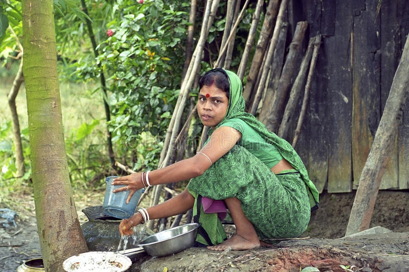 Bengali woman during dish washing outside poor hut. Bangladesh Charburhan village on the island Charkajal, Bay of Bengal: portrait of a Bengali woman in colorful royalty free stock photos