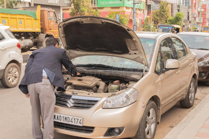 Bengaluru, India 27,2019 Juni: Zakenman die aan insepct zijn gebroken auto aan wegkant proberen in Bengaluru, India royalty-vrije stock afbeelding