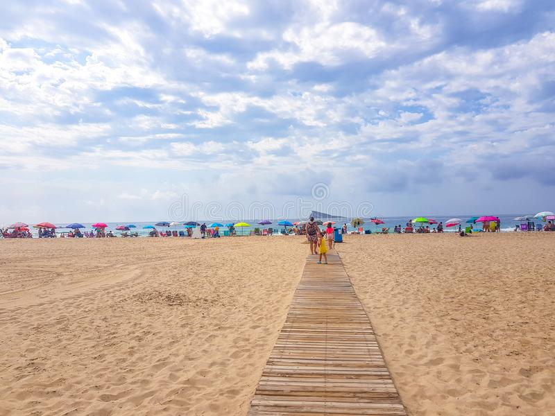 Benidorm, España; 12 de julio de 2018: Entrada a la playa por la calzada de madera con los paraguas, los turistas y el fondo del  foto de archivo libre de regalías