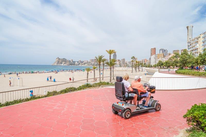 Benidorm, Espanha, o 17 de junho de 2019: Pares superiores no 'trotinette' da mobilidade que aprecia férias de verão em Benidorm, imagens de stock