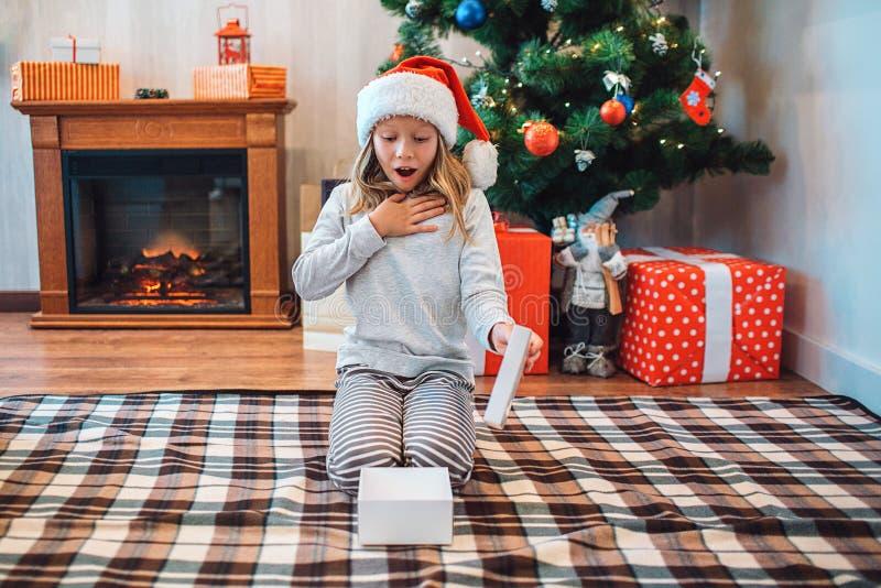 Benieuwd geweeste en verbaasde kindzitting op knieën en het bekijken geopende witte doos Zij houdt bovenkant ter beschikking van  stock fotografie