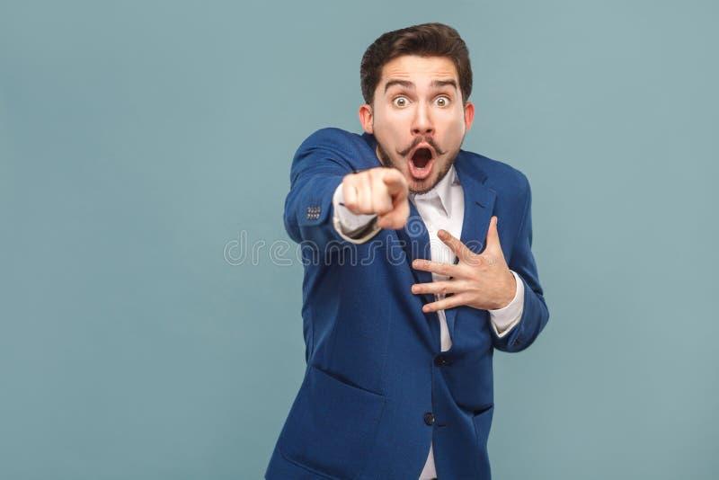 Benieuwd geweeste mens die vinger richten op camera met geschokt gezicht stock foto