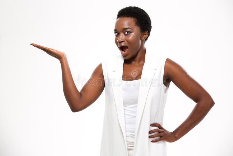 Benieuwd geweeste opgewekte Afrikaanse vrouw die en copyspce zich op palm bevinden houden royalty-vrije stock foto's