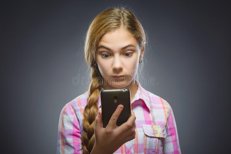 Benieuwd zijnd meisje die mobiele telefoon of cellphone bekijken Close-upportret van tiener in toevallig overhemd op grijze achte royalty-vrije stock fotografie