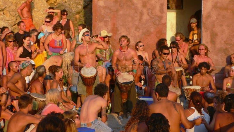 Benirras wyrzucać na brzeg, Ibiza Hiszpania, Lipiec, - 23, 2006: Udziały ludzie ogląda zmierzch podczas gdy bawić się bębeny i in zdjęcia stock