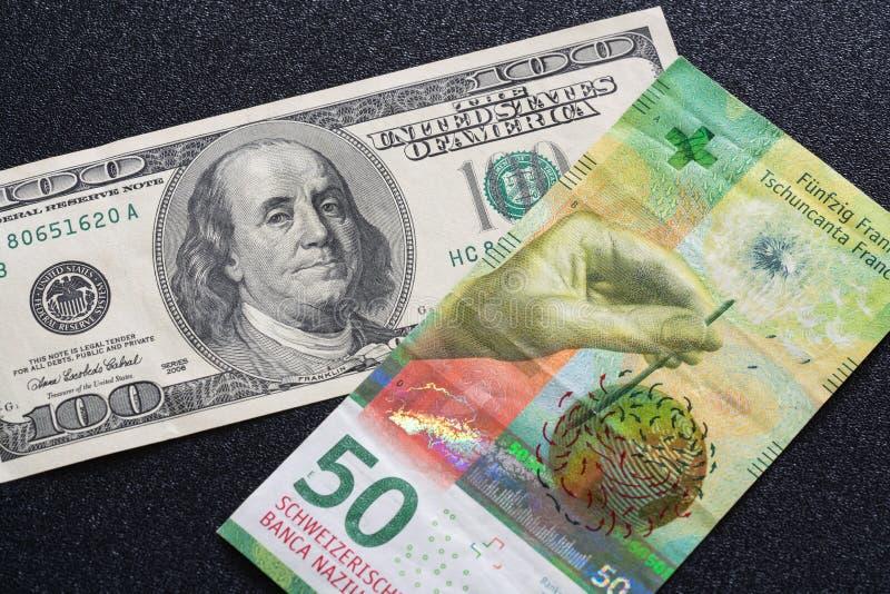 Benjamin Franklin der Zauberer eine Hundertdollar-Rechnung und 50 Schweizer Franken lizenzfreie stockbilder