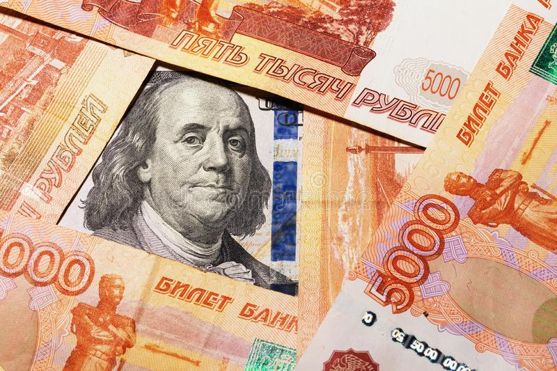 Benjamin Franklin on a hundred dollar bill surrounded by Russian rubles with a face value of five thousand each royalty free stock photo