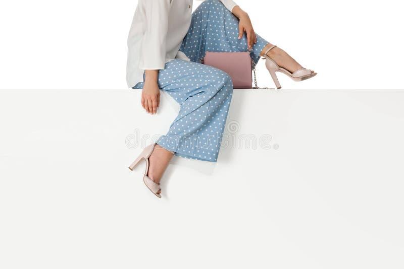 Benkvinnan som b?r h?ga h?l, skor sammantr?de p? b?nk royaltyfri bild