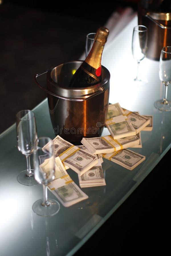 Benna di champagne vicino a contanti fotografie stock