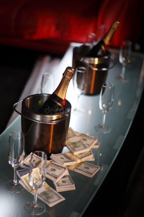 Benna di champagne vicino a contanti fotografia stock libera da diritti
