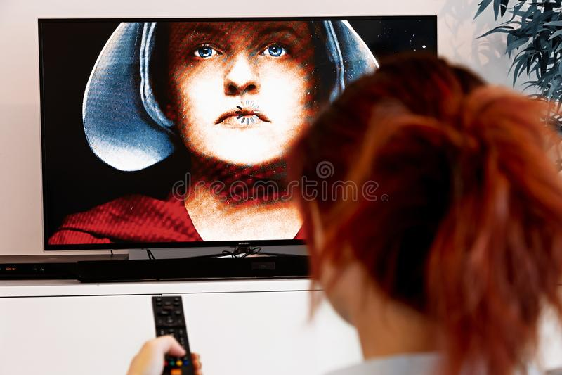 Benon, França - 30 de dezembro de 2018: Mulher que guarda um telecontrole da tevê e para olhar o conto do handmaid O conto do han imagem de stock royalty free