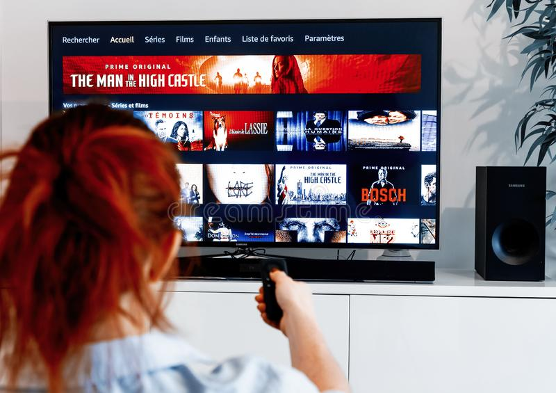 Redhead woman sitting in her living room and holding a television remote control facing a royalty free stock photo