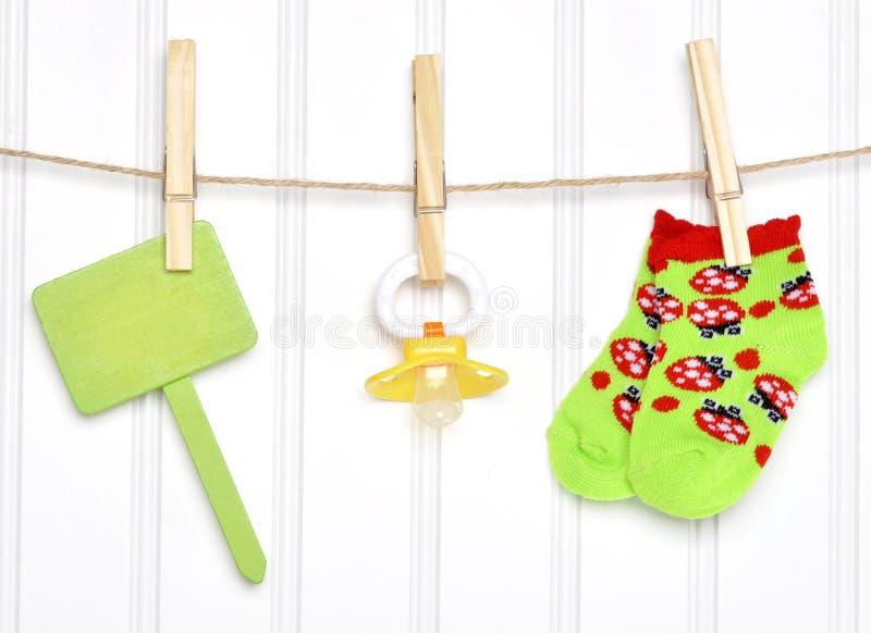 Bens do bebê e sinal em branco em um Clothesline fotos de stock