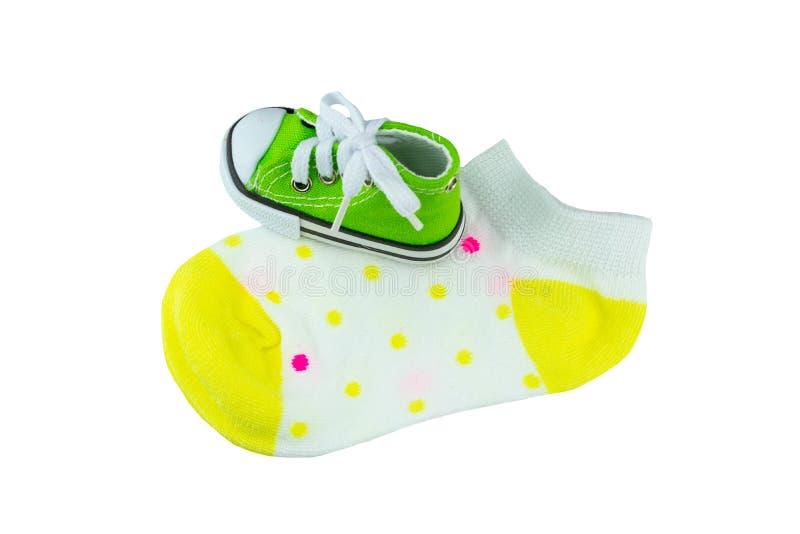 Bens do bebê Peúgas coloridas do bebê do close up e uma sapata de bebê isolada foto de stock