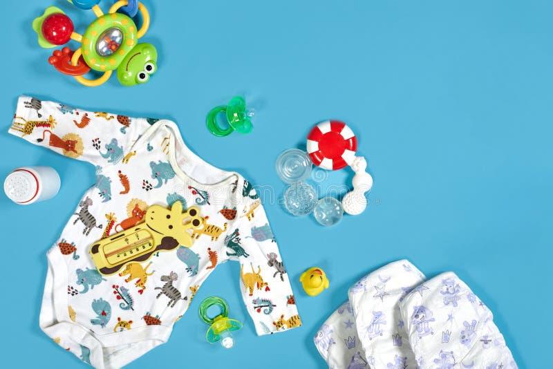 Bens dos bebês: tecido de pano, pó de bebê, nibbler, creme, teether, soother, brinquedo do bebê no fundo azul Copie o espaço alto imagens de stock