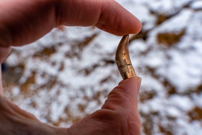 Bent Bullet After Being Shot, in der Hand halten, Sande und Schnee im Hintergrund - mit ballistischen Kennzeichen stockfotos