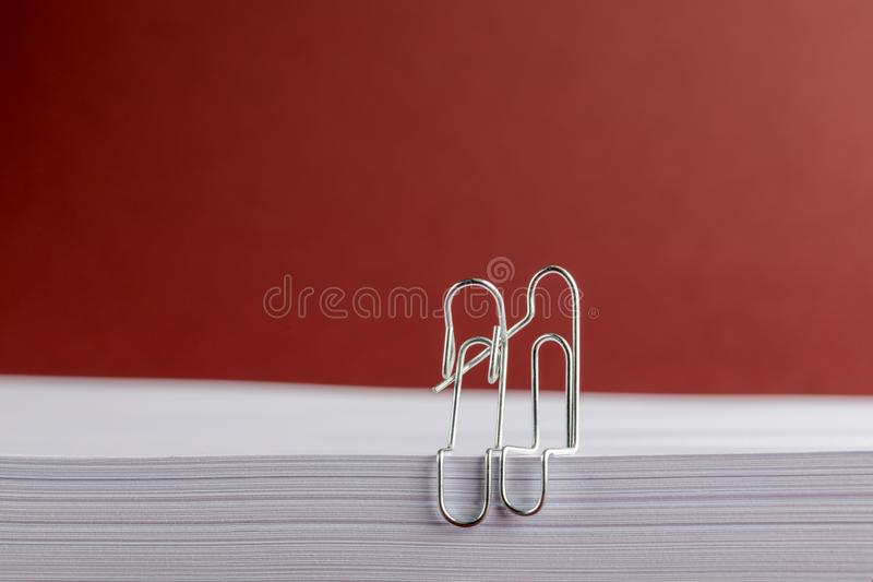 Bent paper Clips Cuddling on White Paper on a Red Background royalty free stock photography